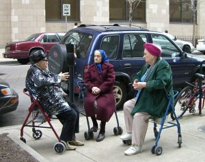 3 older ladies sitting on their walker chairs