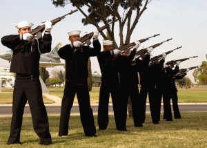 A Navy Honor Guard renders a twenty-one gun salute during a memorial service .